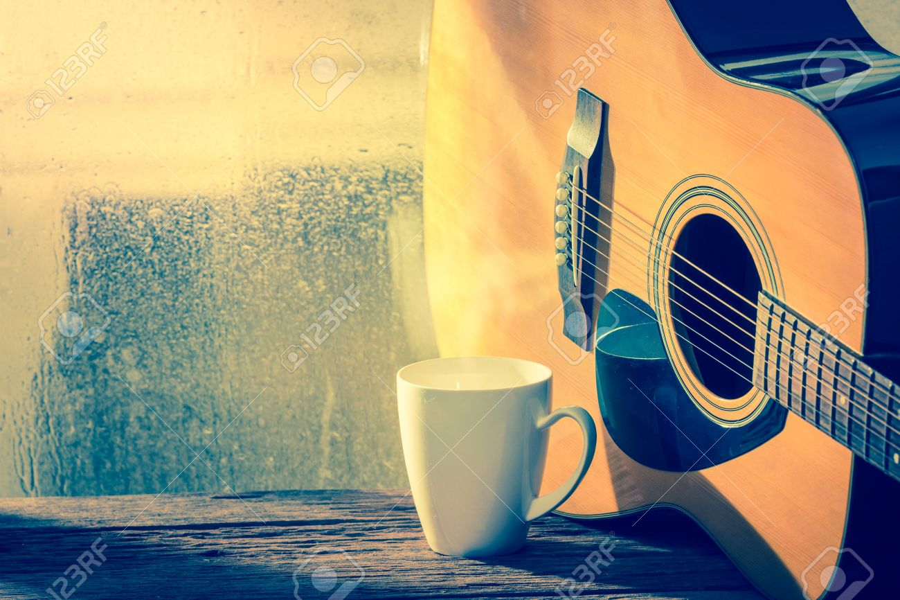 Coffee cup and acoustic guitar next the window with drop water - 31363875