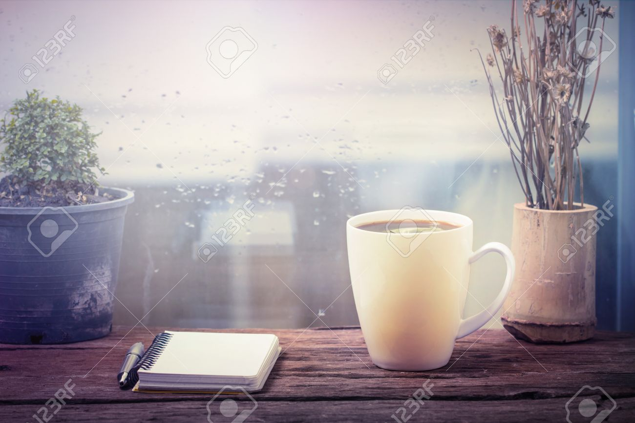 Steaming coffee cup on a rainy day window background - 34556310