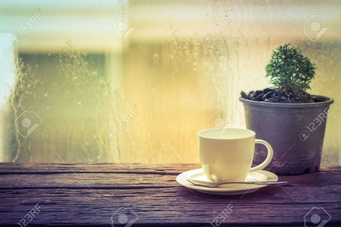 Coffee cup on a rainy day window background - 34556323
