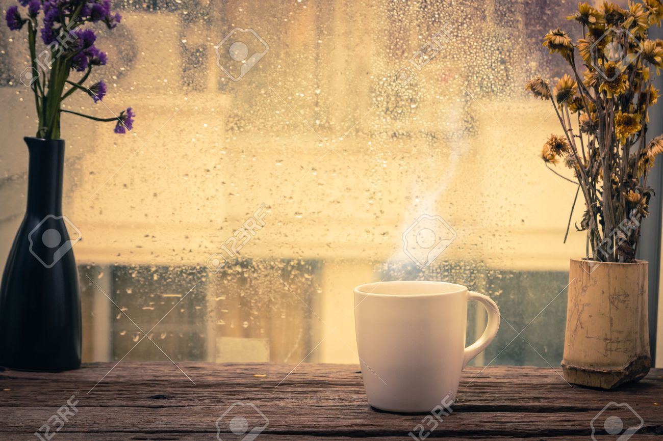 Steaming coffee cup on a rainy day window background - 39430563