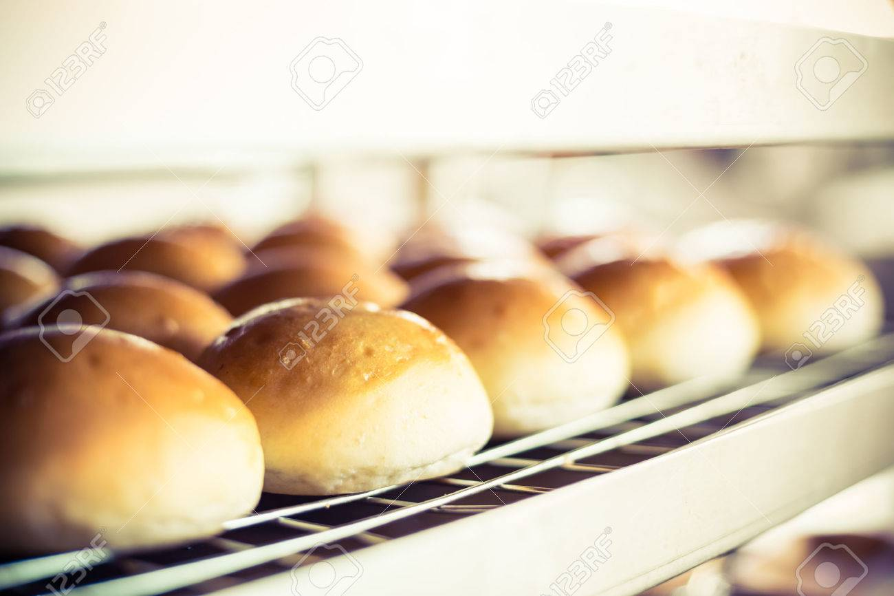 Delicious buns with crust on blurred bakery indoor background. - 53586014