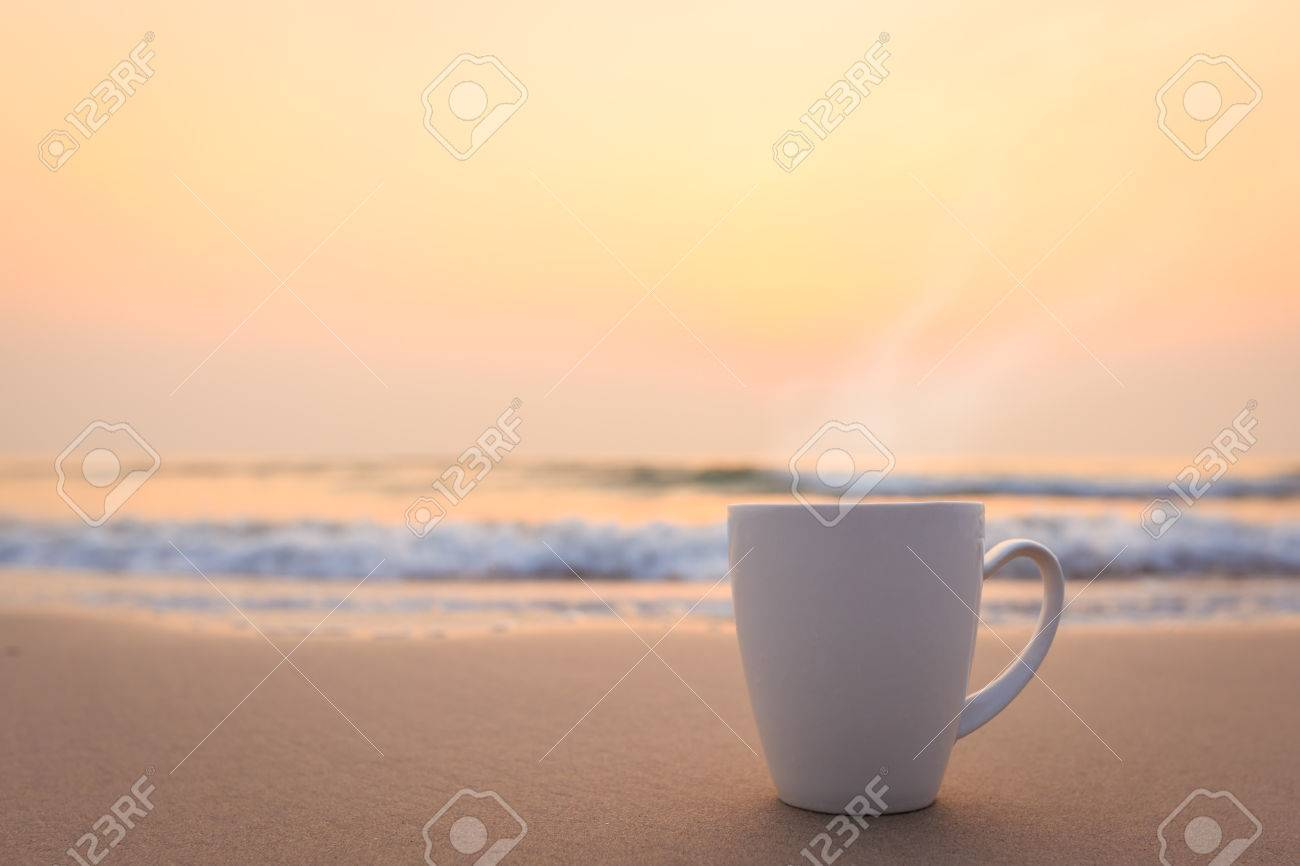 Close up white coffee cup on sand beach and view of sunset or sunrise background,peaceful - 57956942