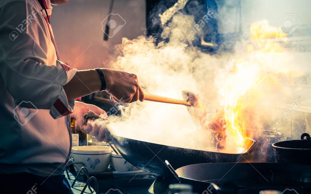 Chef is stirring vegetables in wok - 81611729