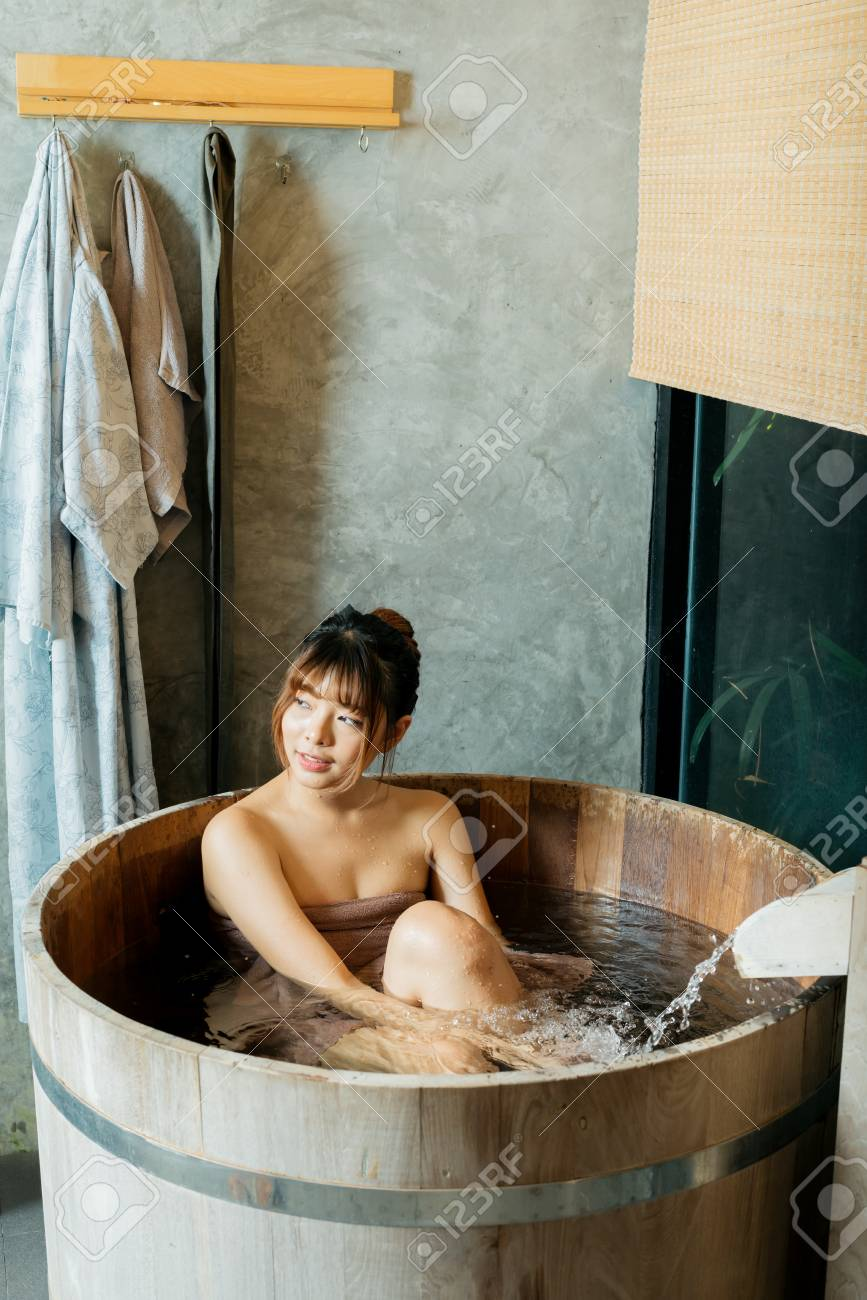 Onsen series: Asian woman taking a bath in wooden bathtub Stock Photo -  96632091
