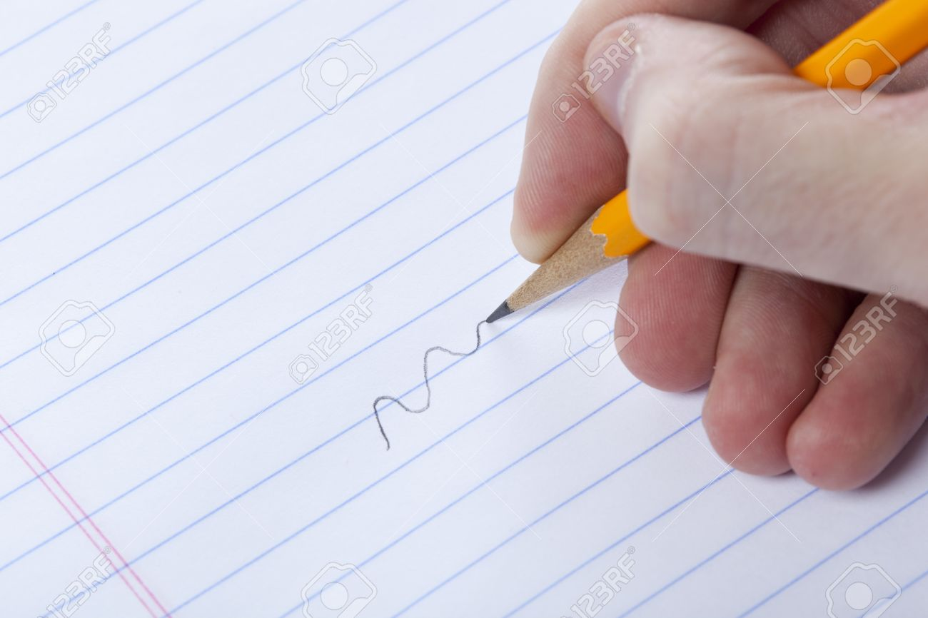a person writing with a yellow pencil on notebook paper stock photo