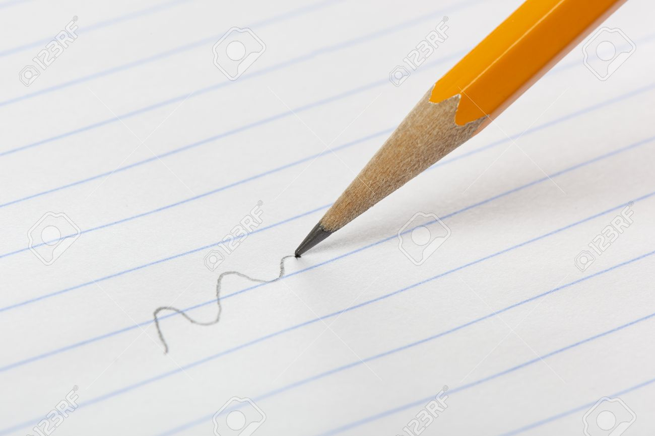 a yellow pencil writing on notebook paper stock photo, picture and