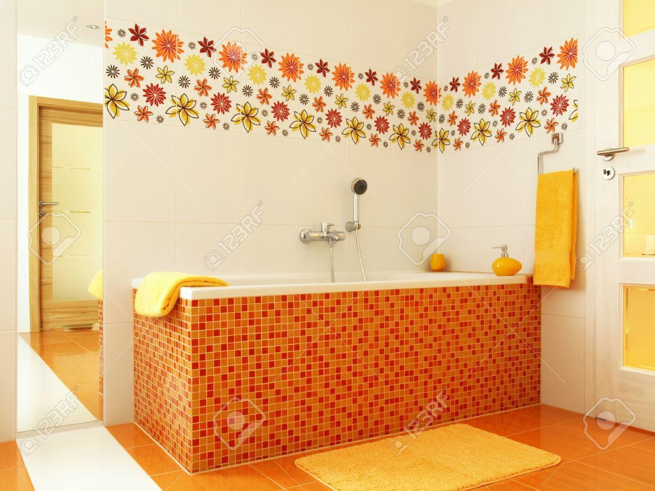 Colorful Bathroom With Orange Mosaic Bathtub And Yellow Towels Stock Photo    13058289
