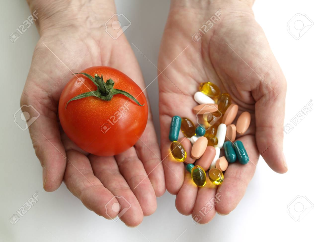 Man holding a vegetable and handfull of supplements - 13318343
