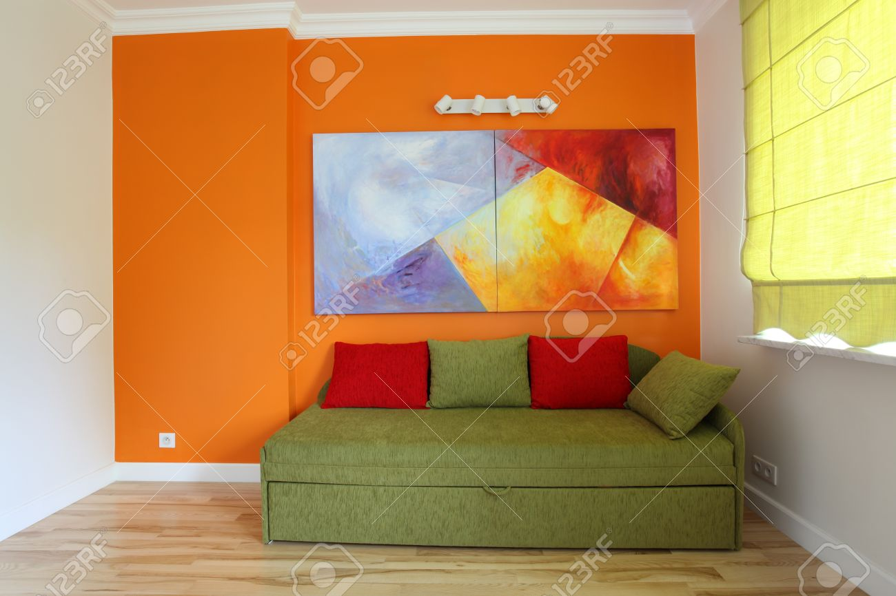 Orange wall and green sofa in teenage room Stock Photo - 15554124