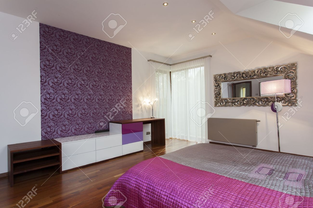 Violet Bedroom With Patterned Wallpaper On One Wall Stock Photo