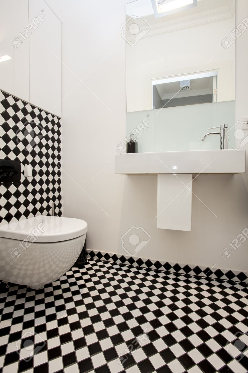 Toilet With A Black And White Tiles Stock Photo Picture And - White toilet with black seat