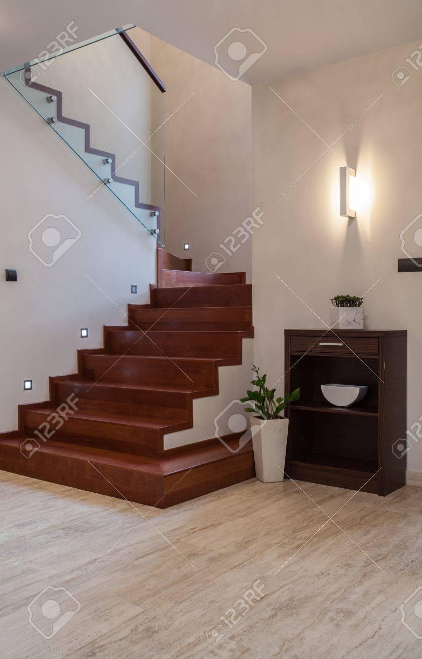 travertino casa escaleras de madera y barrera de vidrio foto de archivo