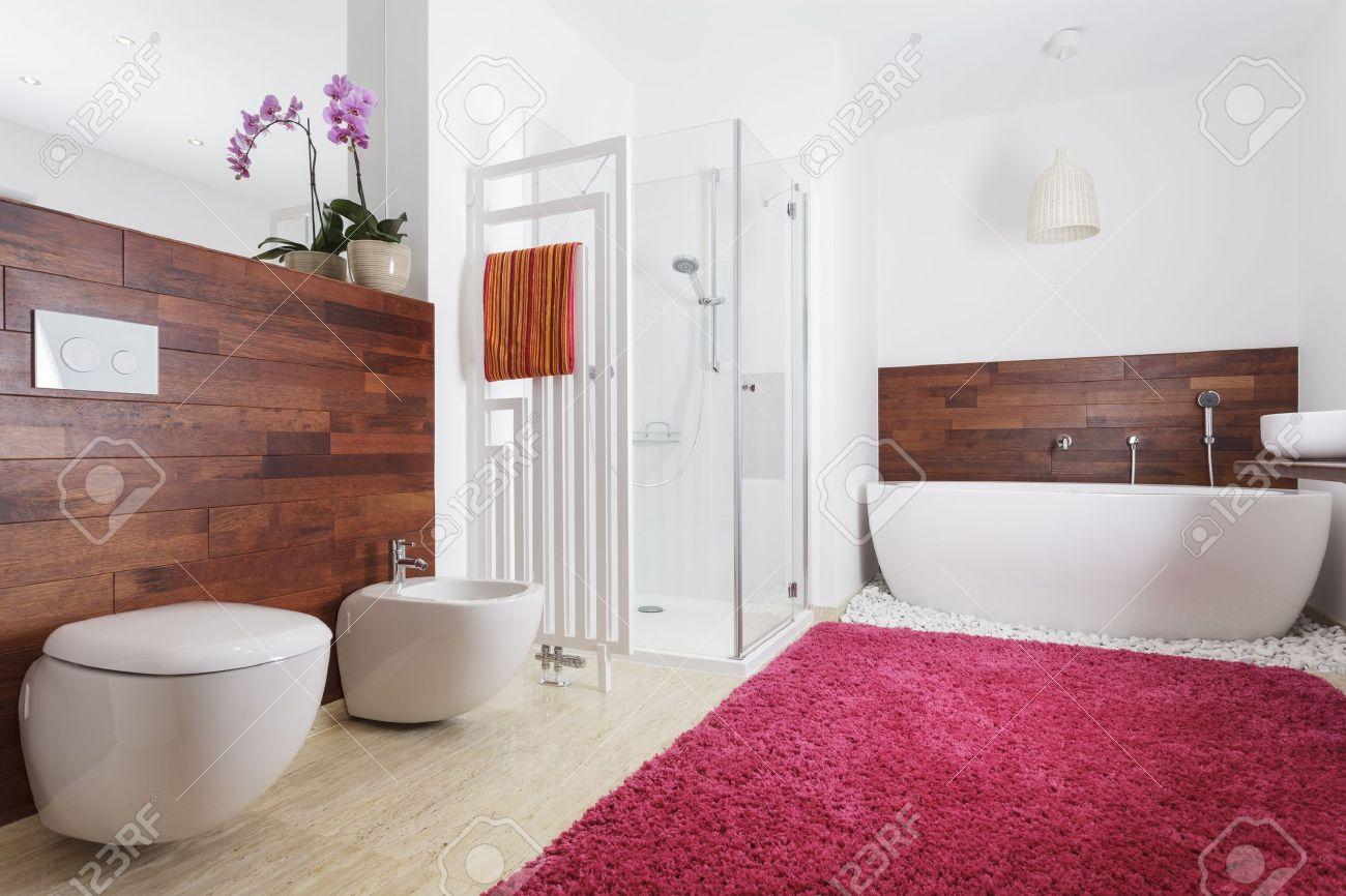 Interiör från ett modernt badrum med rosa mattan och trävägg ...