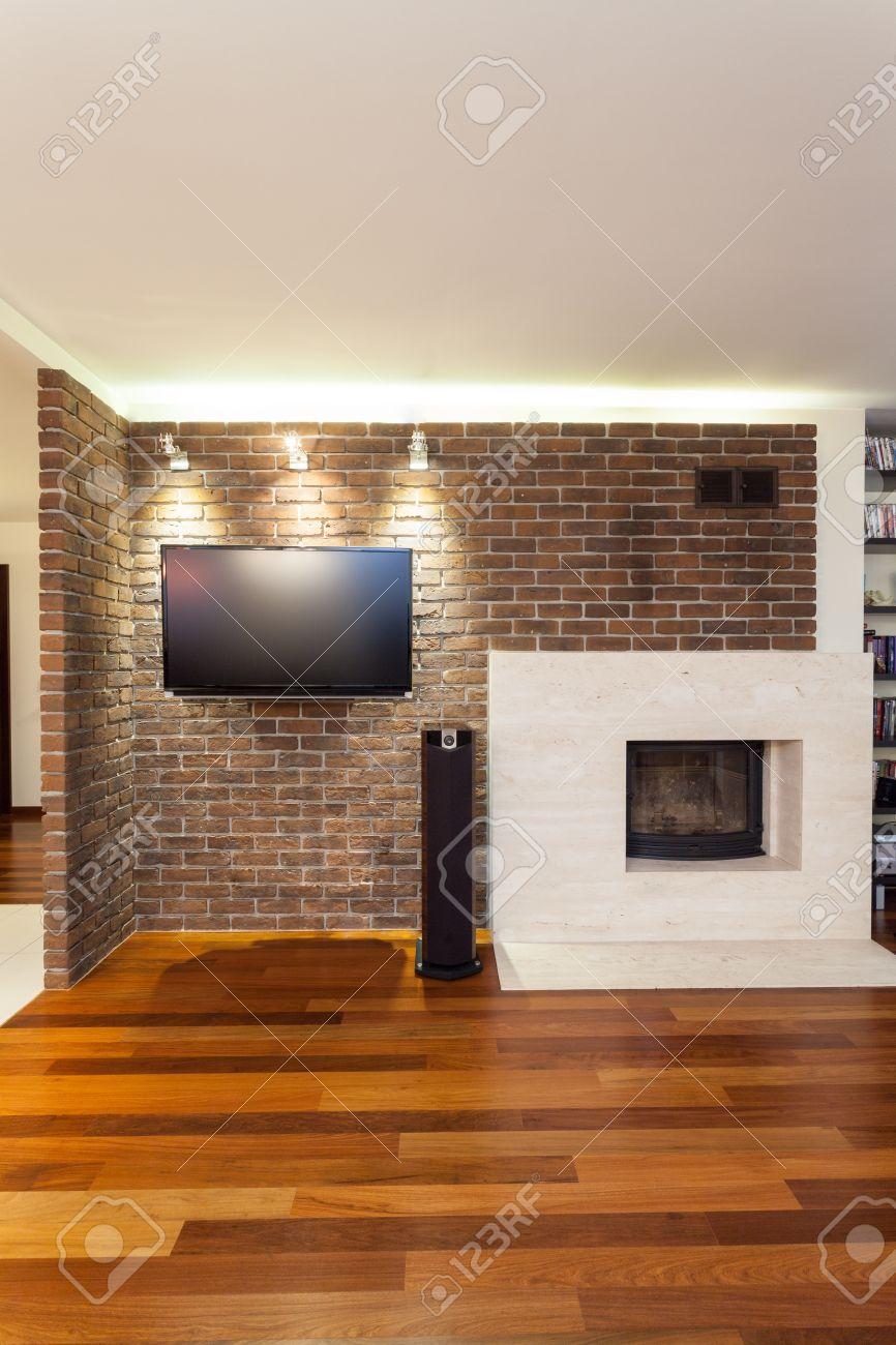 Ruim appartement   bakstenen muur met open haard en tv royalty ...