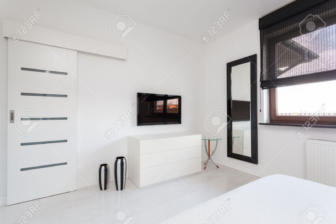 Stock Photo   Vibrant Cottage   White Commode And Black Tv In Bedroom