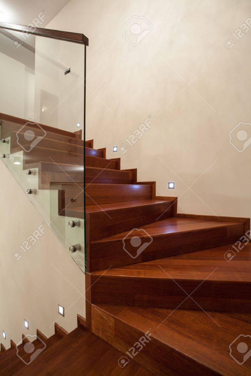 travertine house- closeup of wooden, glass stairs in modern