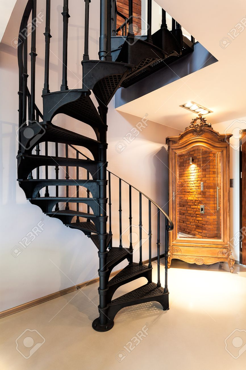metal spiral staircase and old fashioned wardrobe stock photo