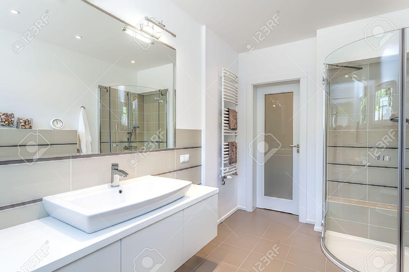 Spazio luminoso   un bagno bianco e beige con un lavandino e una ...