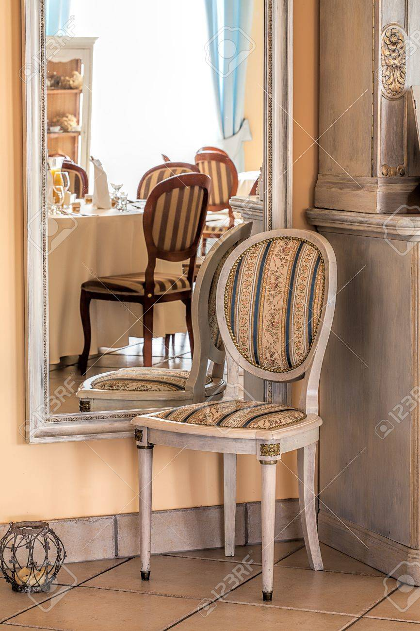 Mediterranean interior - a stripped chair by a framed mirror Stock Photo - 21363371