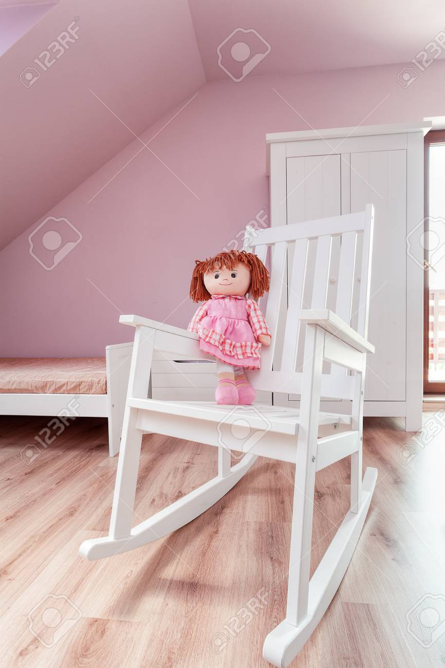 stadtwohnung - rosa puppe auf einem weißen schaukelstuhl lizenzfreie