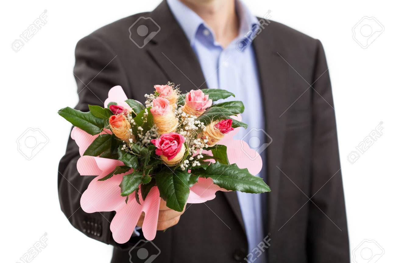 Man In Suit Holding Bouquet Of Flowers For Apology Stock Photo