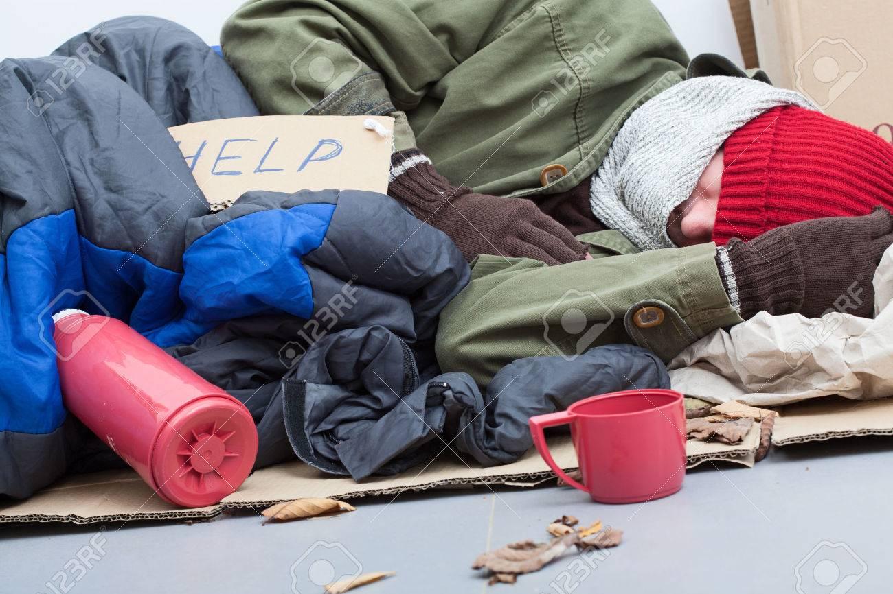Homeless man sleeping on cardboard with sleeping bag and thermos Stock Photo - 23049409