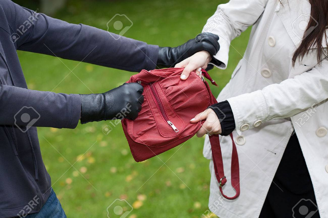 Thief is assaulting a girl to steal a handbag Stock Photo - 23080324