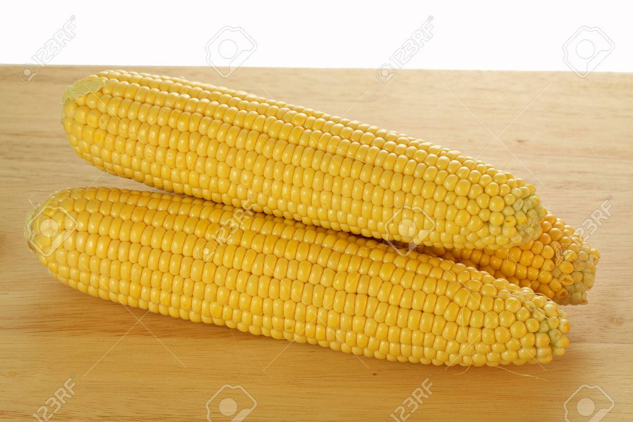 Three yellow conr cobs on the plank Stock Photo - 23256296