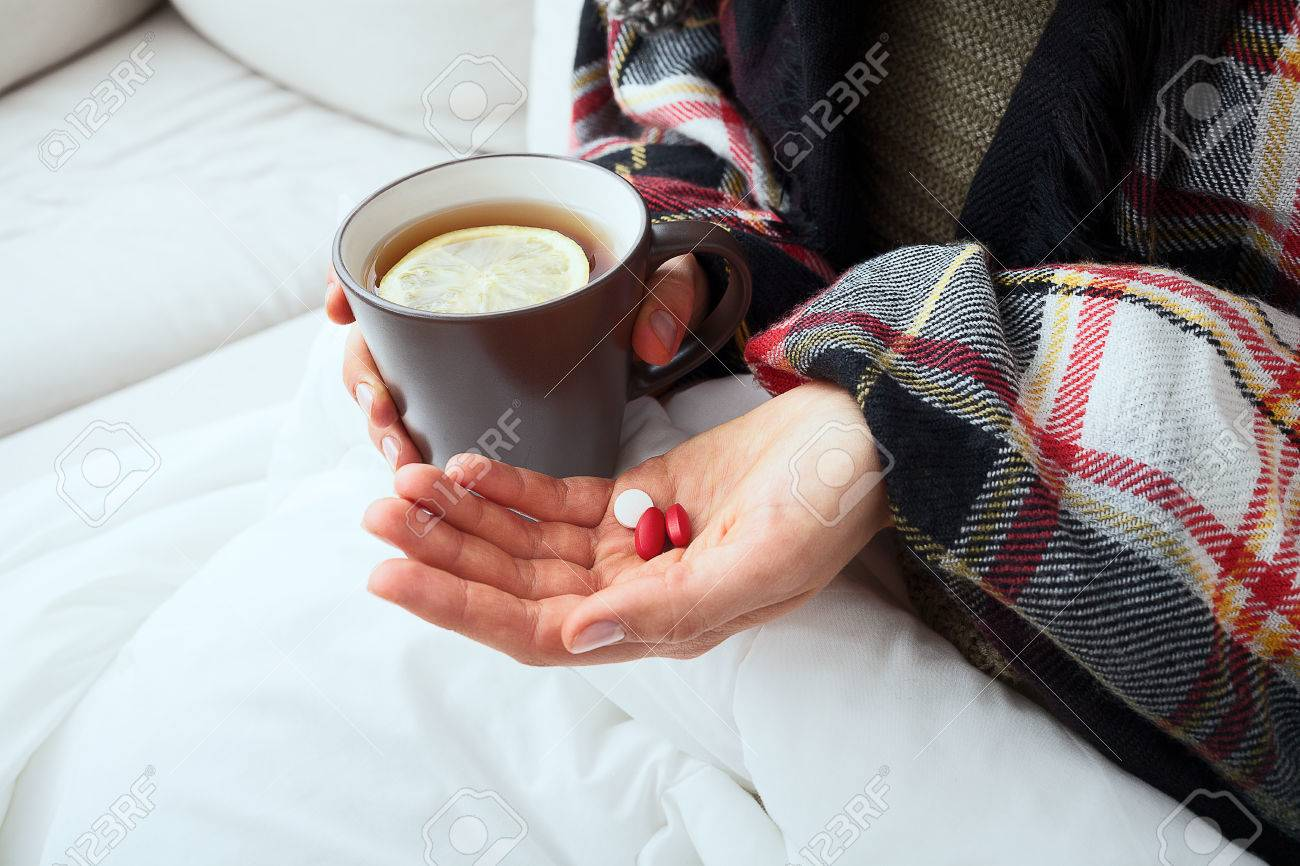 Sick person is taking medicines and drinking hot tea with lemon Stock Photo - 23256350