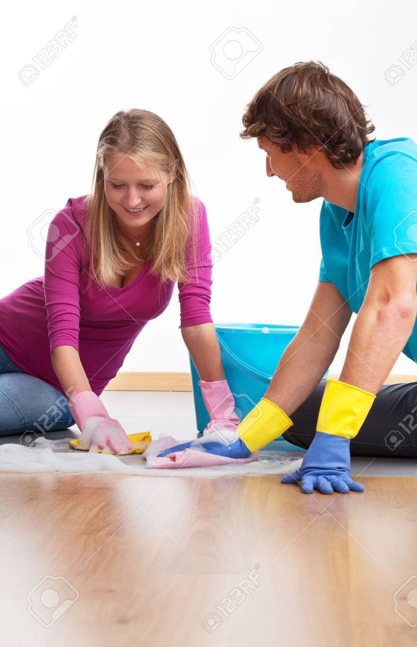 Young couple cleaning the floor and chatting Stock Photo - 23926894