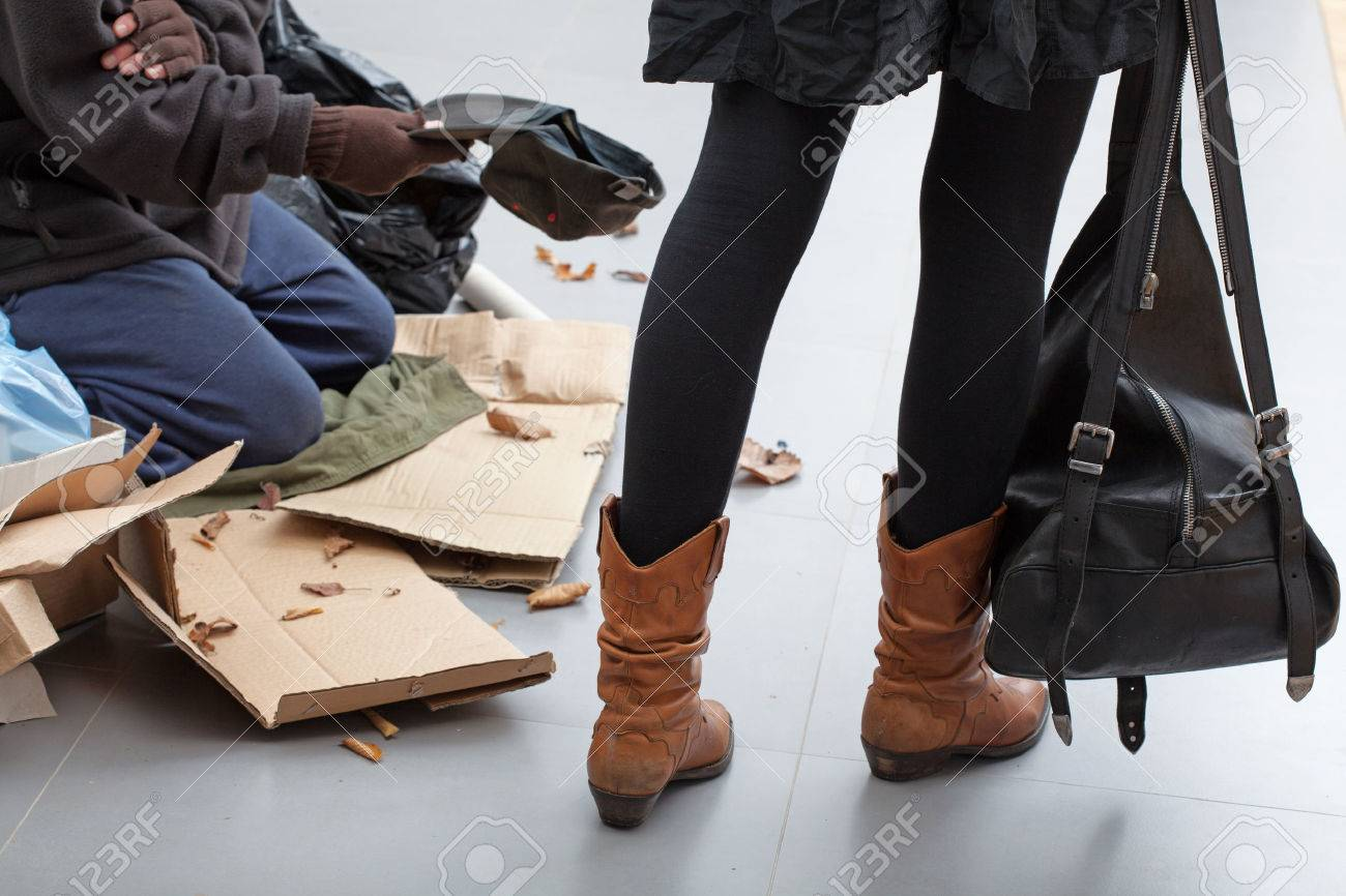 Beggar sitting on a crowded street passed by women Stock Photo - 24368929