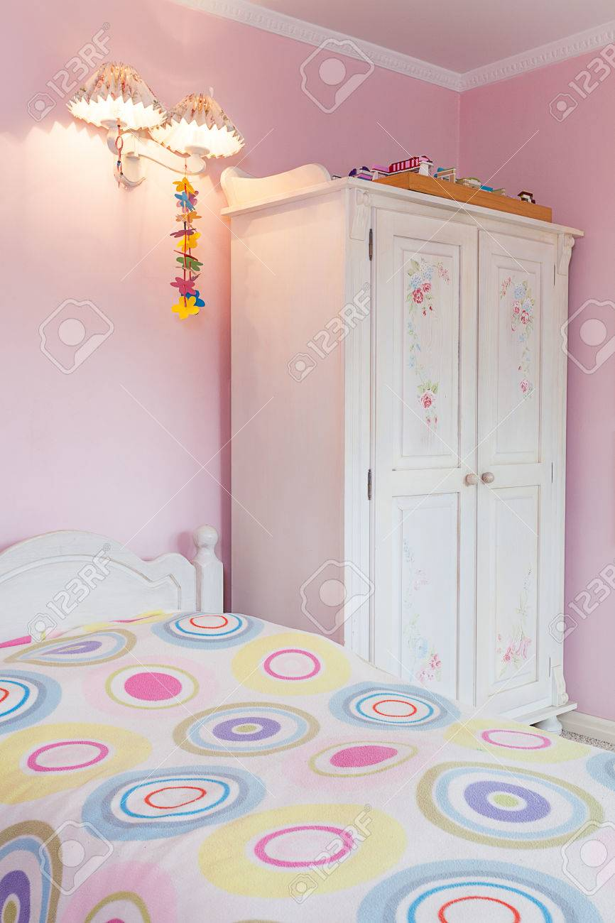 Vintage mansion - a girly bedroom with a colorful bed and a white wardrobe Stock Photo - 24368967