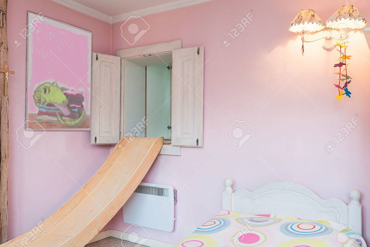 Vintage mansion - apink wall of a girl's bedroom with a slide, a lamp and a painting Stock Photo - 24368968