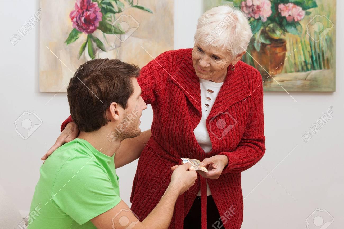 grandma giving pocket money for her grandson stock photo picture
