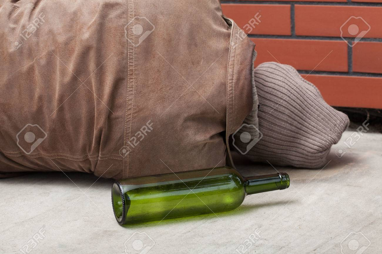 A lying drunkard and and empty bottle Stock Photo - 24492785