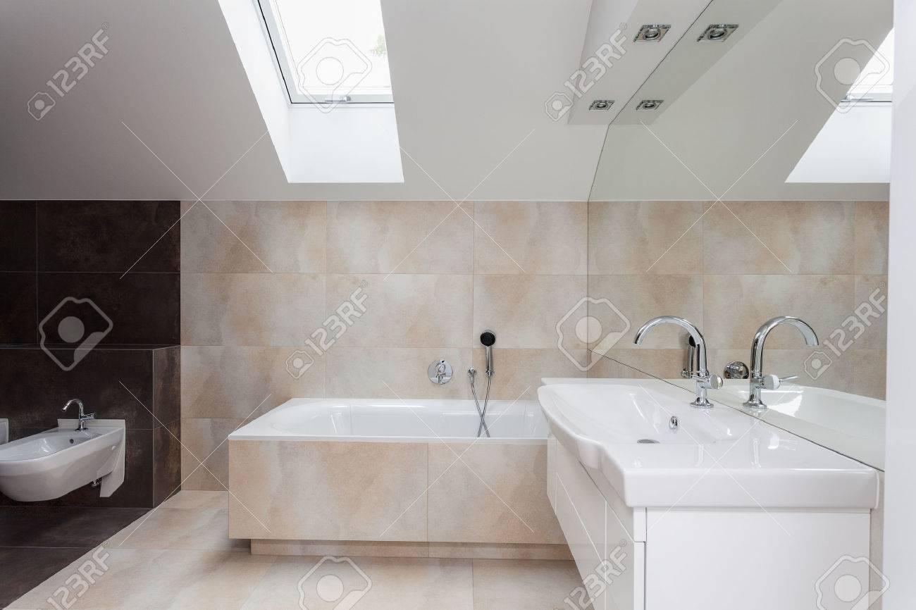 Salle de bains intérieure avec des carreaux beige et marron sur les murs
