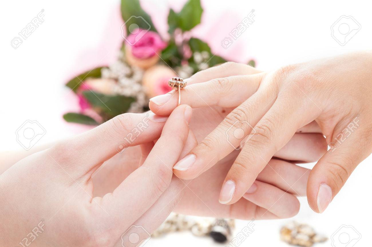 A Man Putting An Engagement Ring On His Fiances Hand Stock Photo