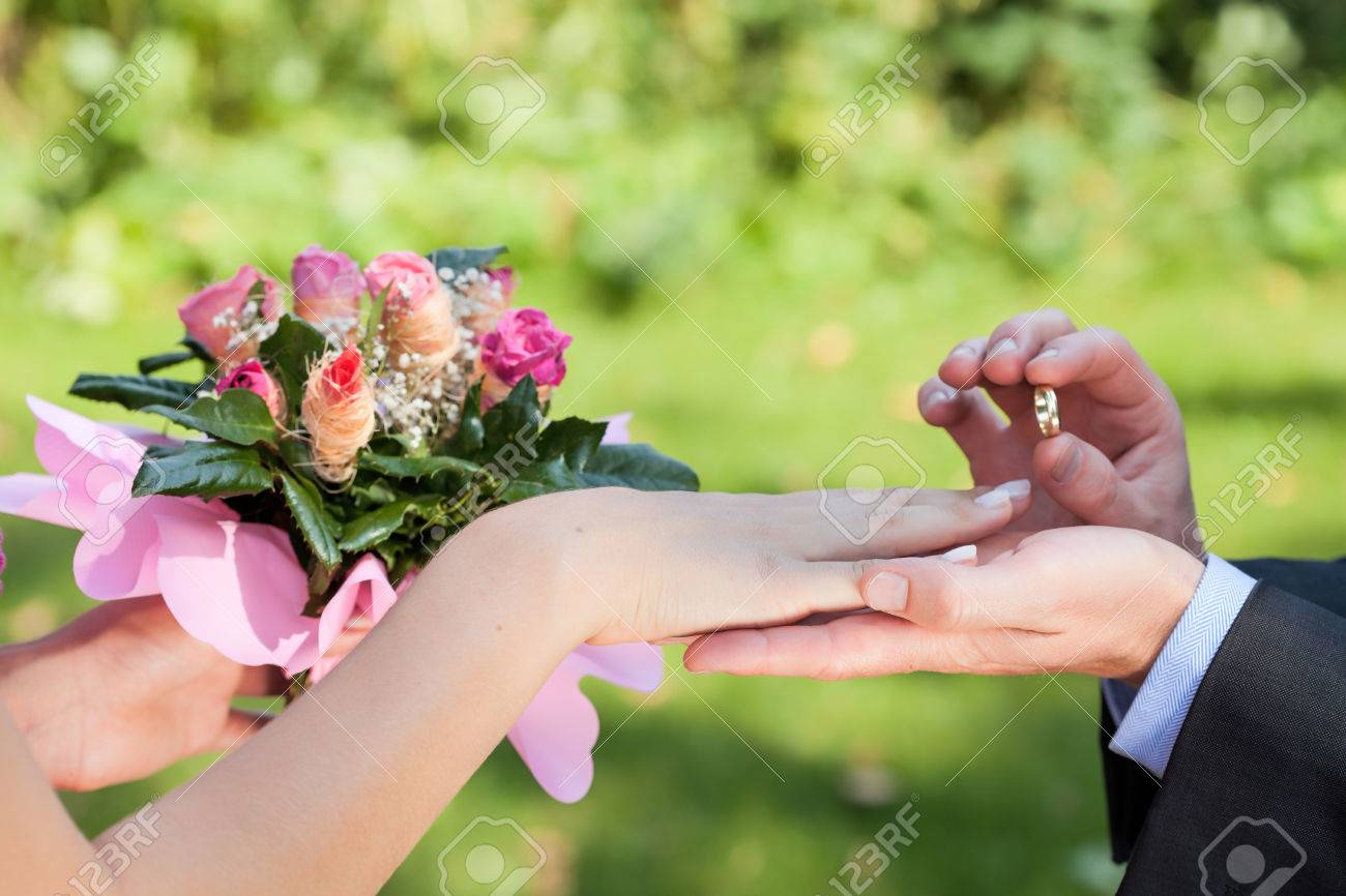 Man Putting A Wedding Ring On His Ladys Hand Closeup Stock Photo
