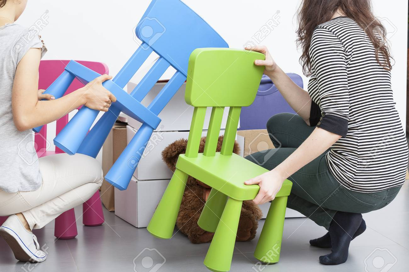 Stock Photo   Two Women Moving Colorful Plastic Chairs For Children