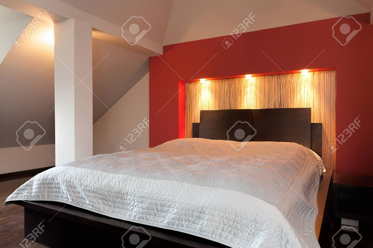 A big white bed by a red lightened wall Stock Photo - 26388800