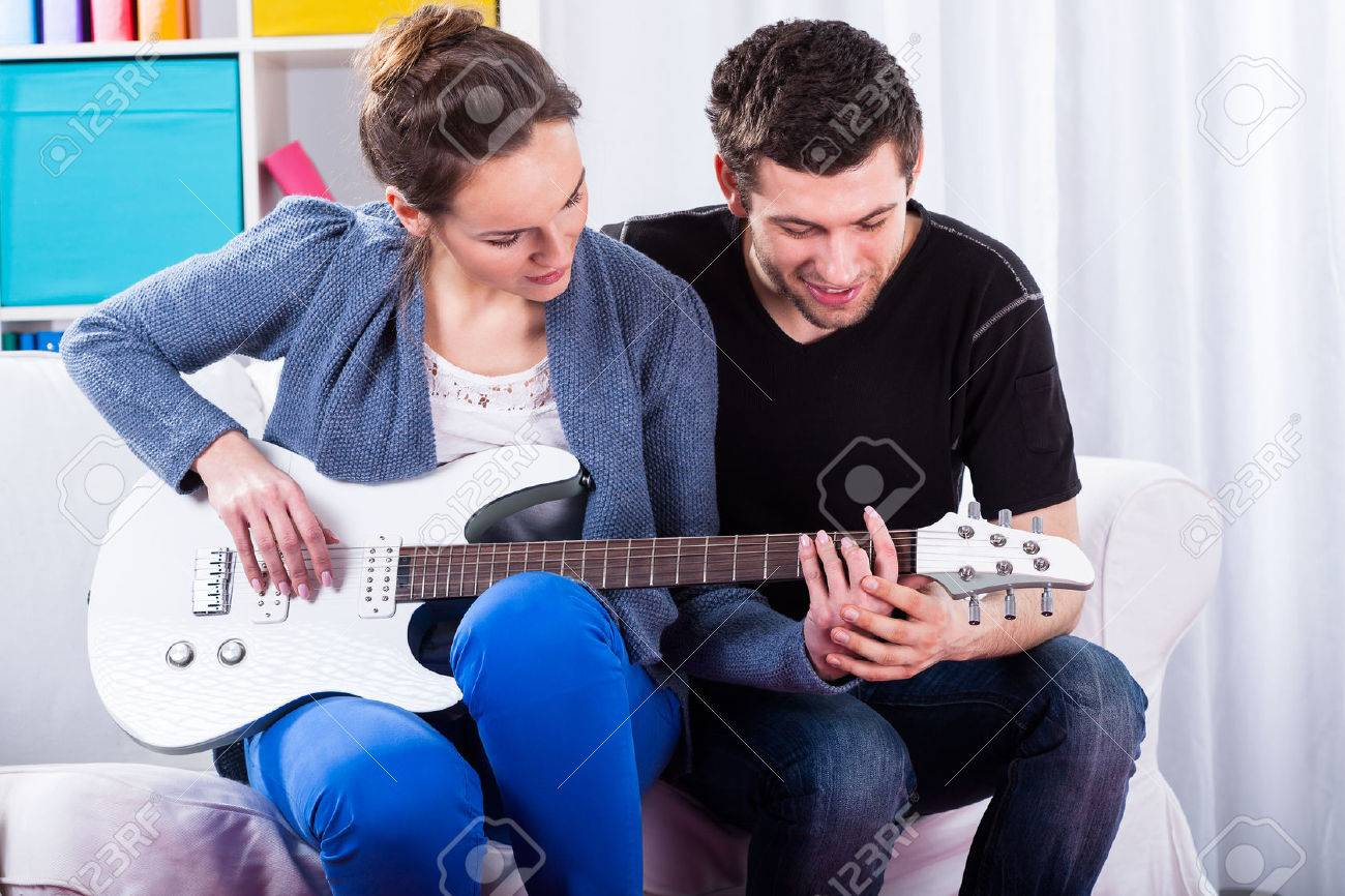 Couple learning to play the guitar, horizontal Stock Photo - 26609815