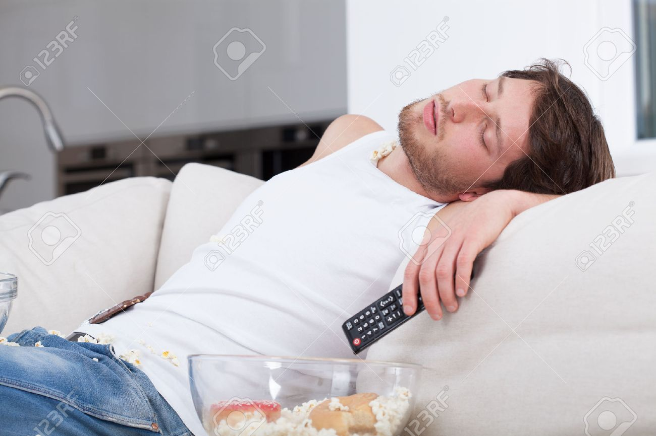 Tired man sleeping on couch in front of tv Stock Photo - 27297561