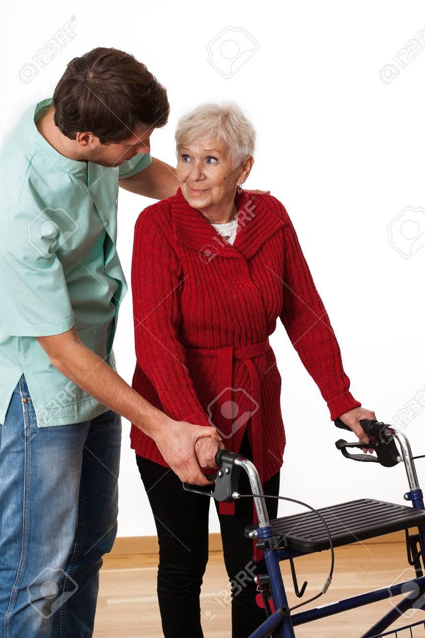 Fisioterapeuta Joven Que Enseña A Vieja Señora Cómo Usar Un Andador ...