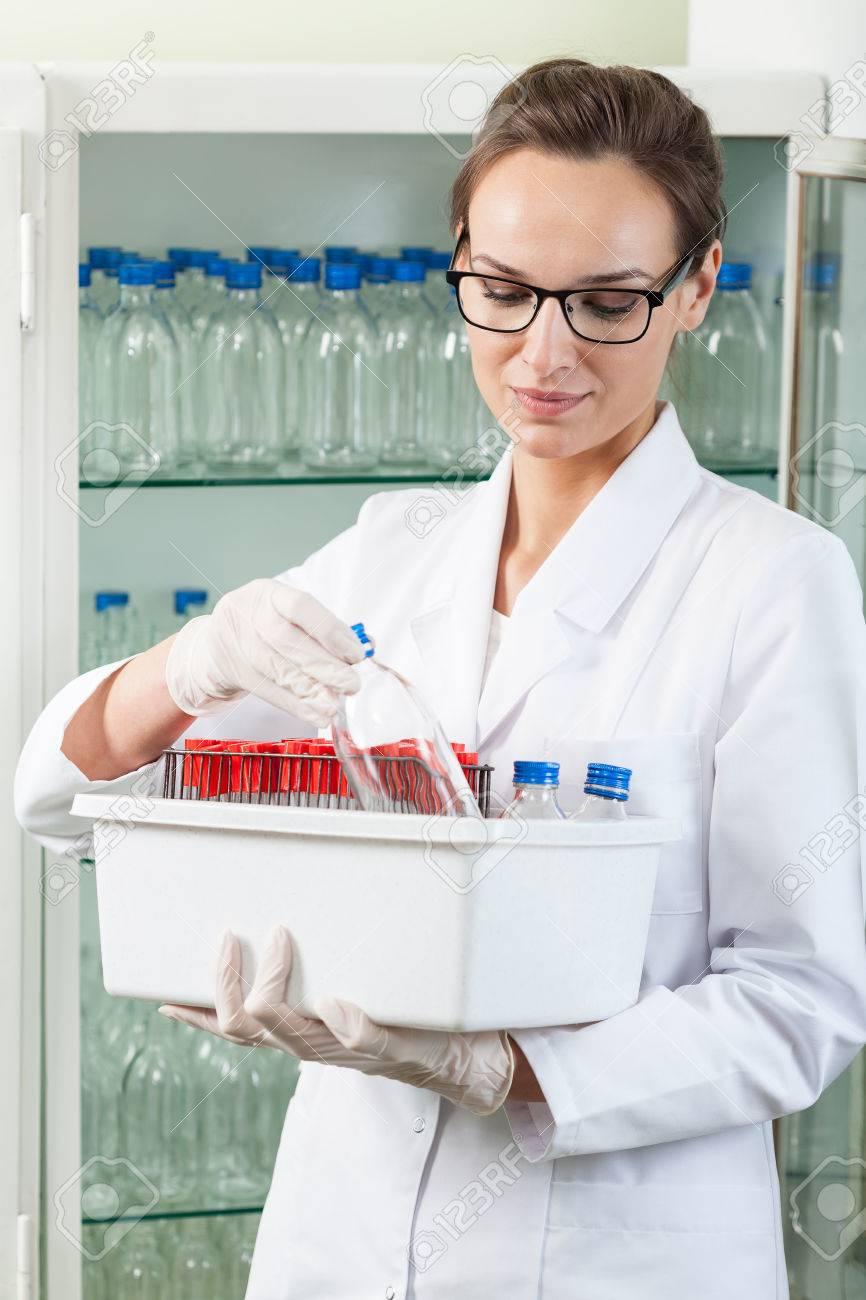 White apron health - Stock Photo Woman In White Apron Holding Box With Laboratory Equipment