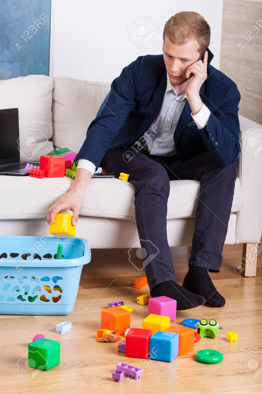 Elegant Man Cleaning Up Toys While Talking On The Phone Stock Photo