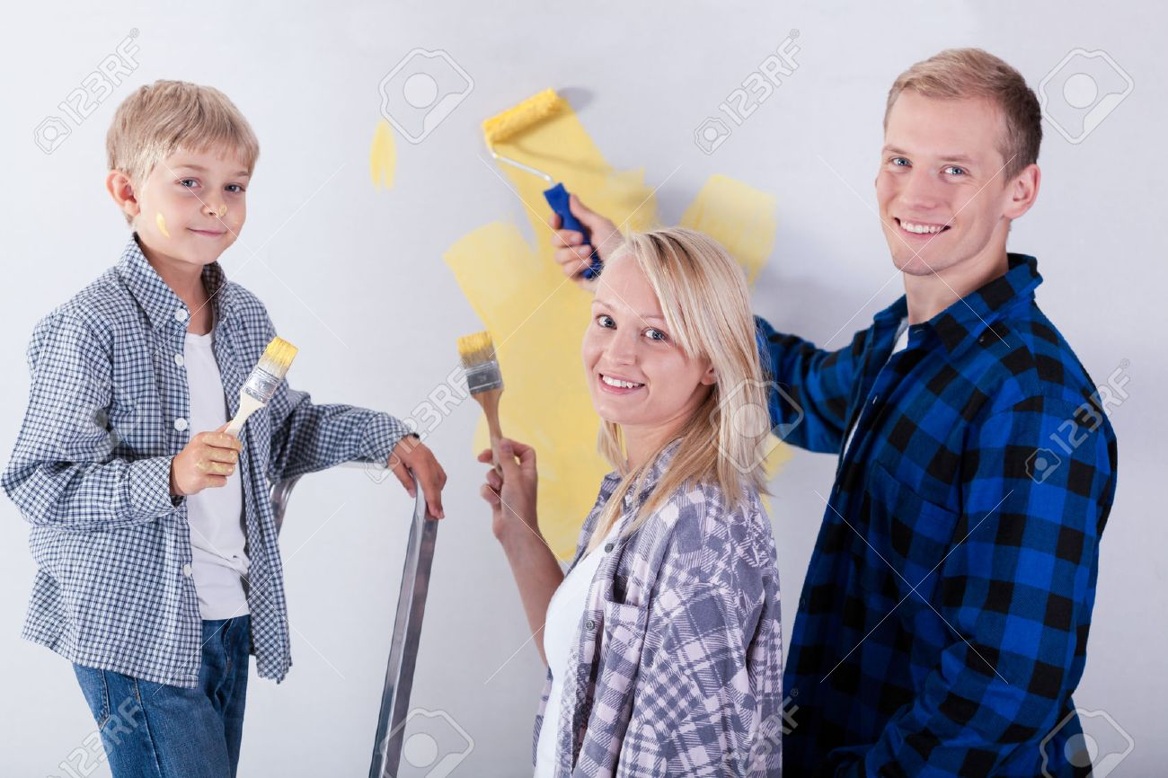 Happy Family Painting Wall In New House Stock Photo