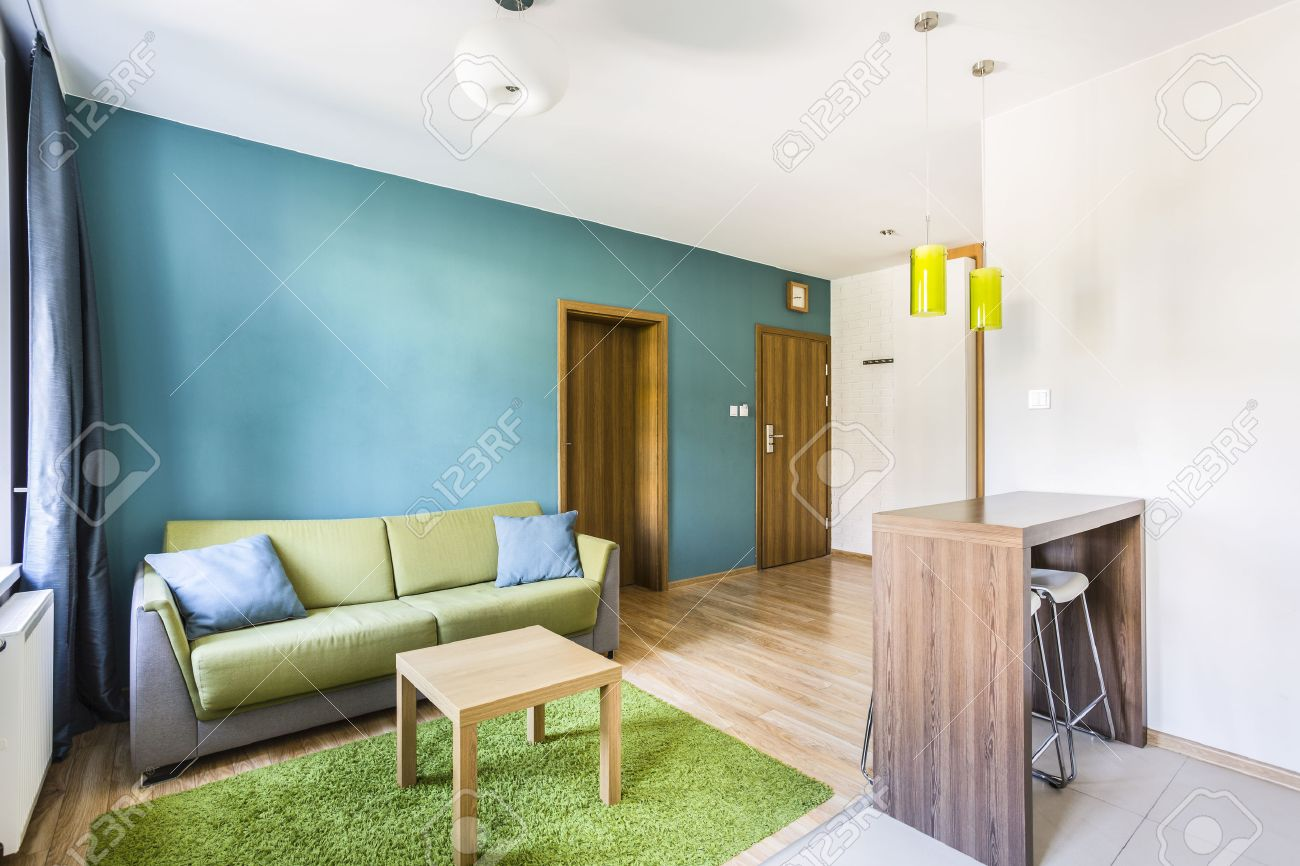 studio apartment interior with cyan wall and green sofa stock