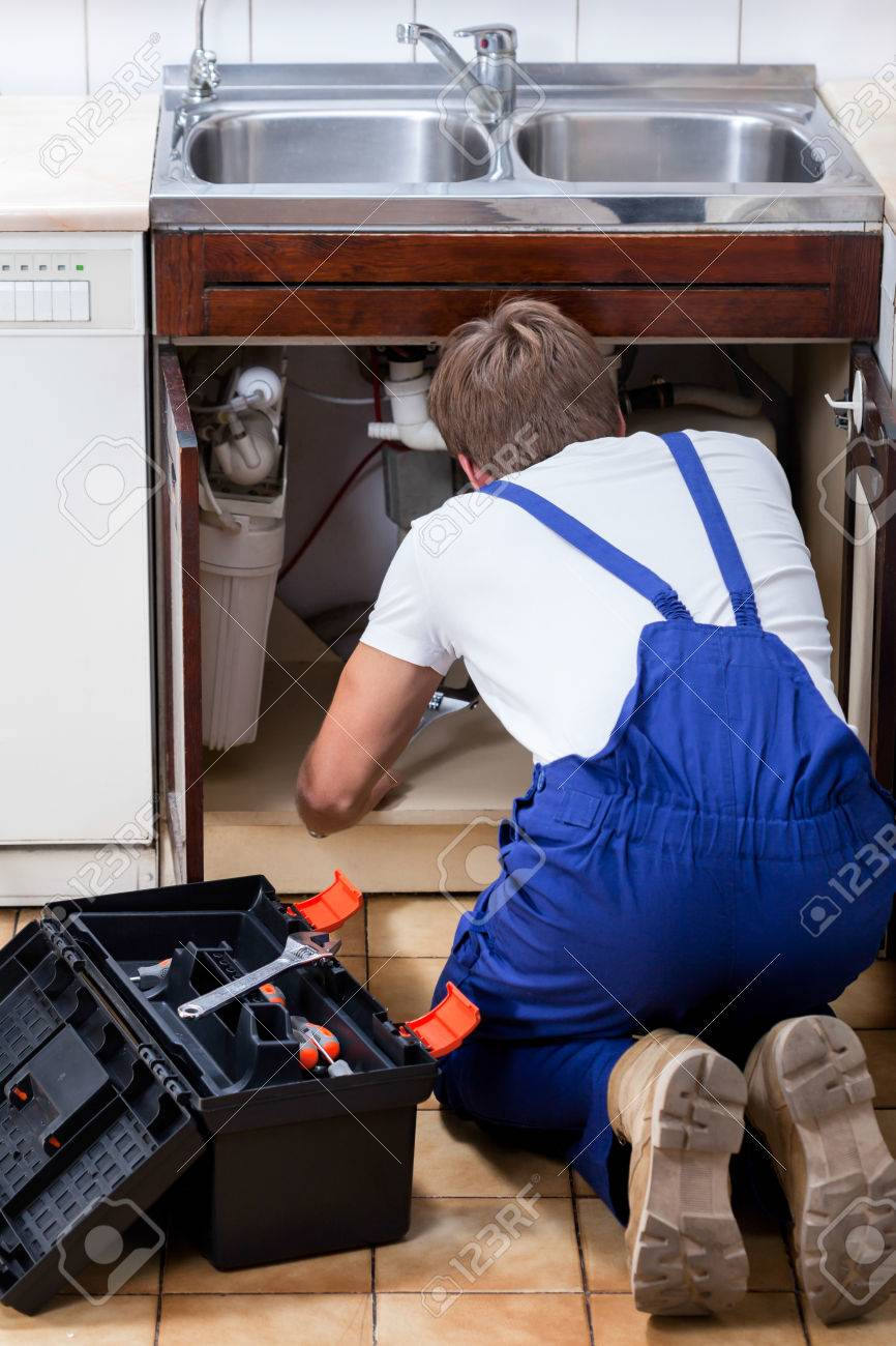 A repair man with a tool box fixing the kitchen sink