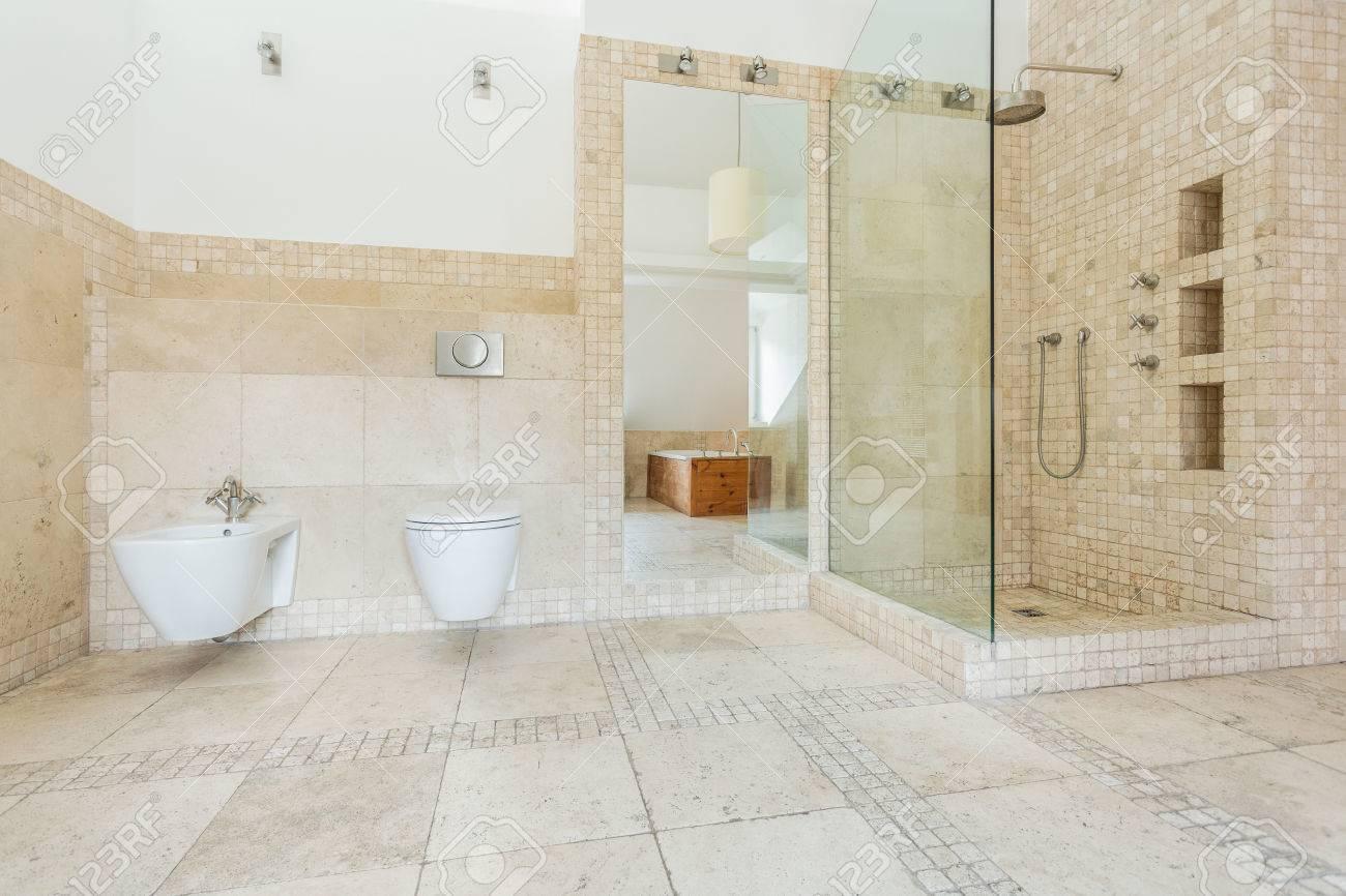 Cuarto de baño con azulejos de color beige en la pared