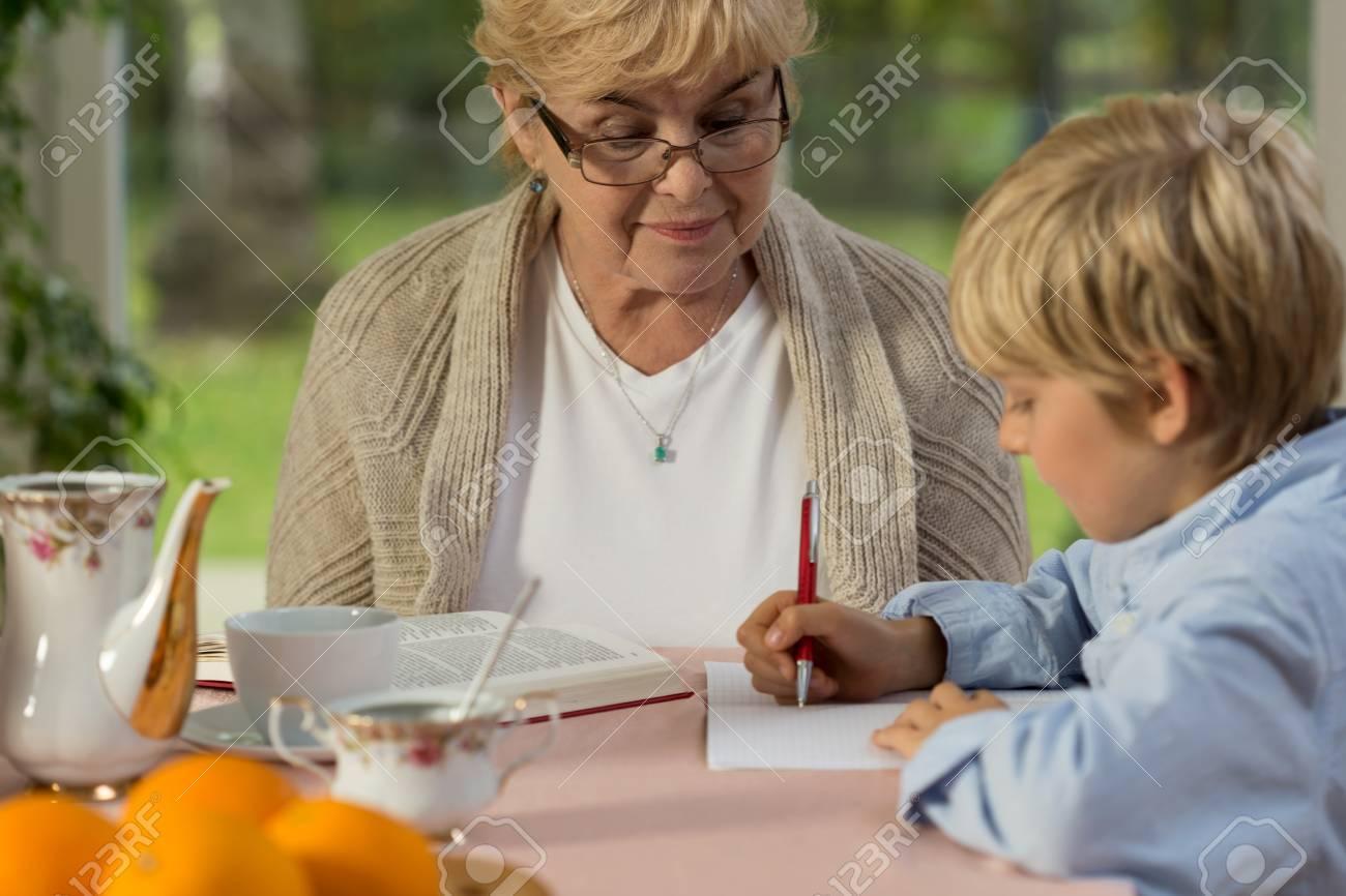 granny boy Little cute boy writing an essay under his granny's eye Stock Photo -  35522013